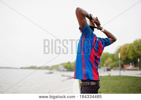 Stylish African American Boy Wear At Cap, Football T-shirt And Sunglasses Stay Against Lake Beach. B