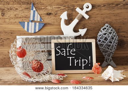 Blackboard With Nautical Summer Decoration And Wooden Background. English Text Safe Trip. Fish, Anchor, Shells And Fishnet For Maritime Contex.