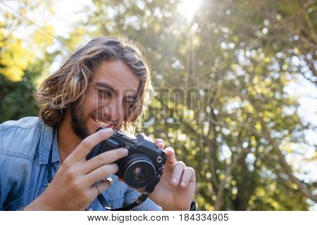 Happy man looking at photos on digital camera in park