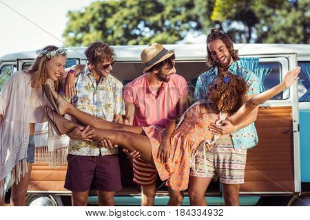 Group of friends lifting woman near campervan in park
