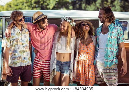 Group of happy friends standing together near campervan in park