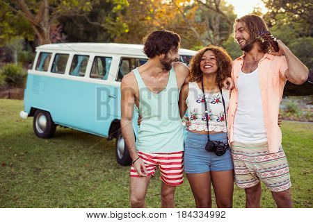 Three friends standing together near campervan in park