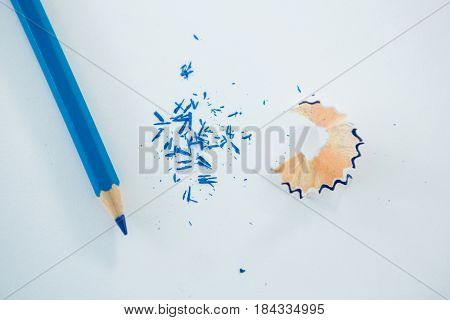 Close-up of red color pencil with pencil shaving on white background
