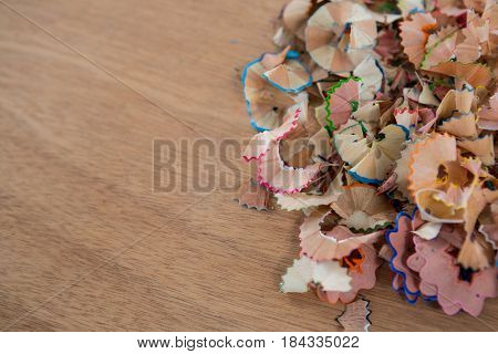 Close-up of colored pencils shavings on wooden background