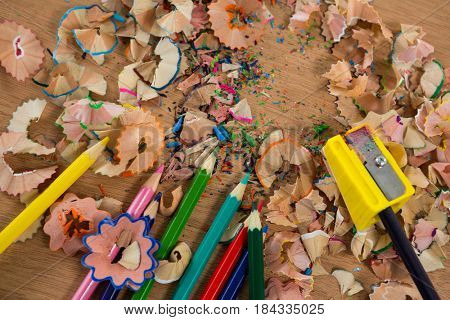 Colored shavings with colored pencils and sharpener on wooden background