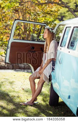 Woman with flower wreath sitting in campervan at park