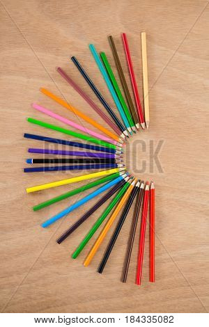 Colored pencils arranged in semi circle on wooden background
