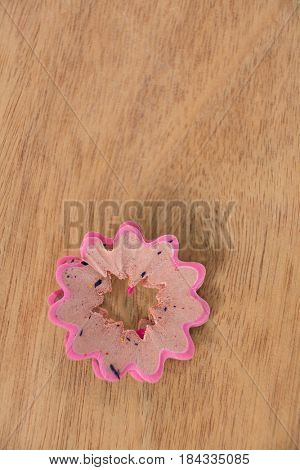 Pink color pencil shaving in a flower shape on a white background