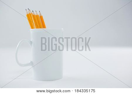 Yellow color pencils kept in mug on white background