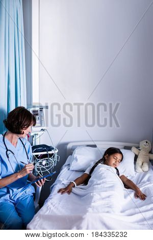 Doctor writing on clipboard while looking at patient in hospital