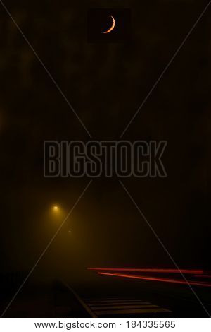 A dense fog on the streets of Brescia and above the fog the moon - Italy
