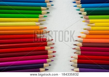 Close-up of colored pencils arranged in a row on white background