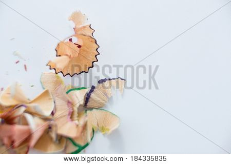 Close-up of colored pencils shavings on a white background