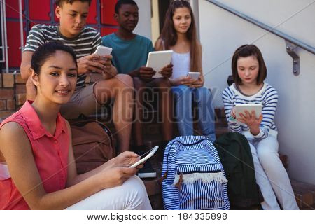 Students using mobile phone and digital tablet on staircase at school