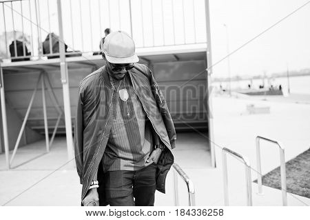 Stylish African American Boy Wear At Cap, Football T-shirt And Sunglasses Posed On Steel Railings. B
