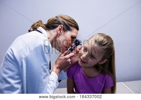 Female doctor examining patient ear with otoscope in hospital