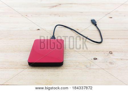 External hard drive for backup on wood background.