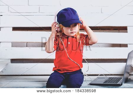 a little kid wearing a headphone near laptop on a white background
