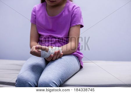 Mid section of girl with injured hand sitting on stretcher bed in hospital