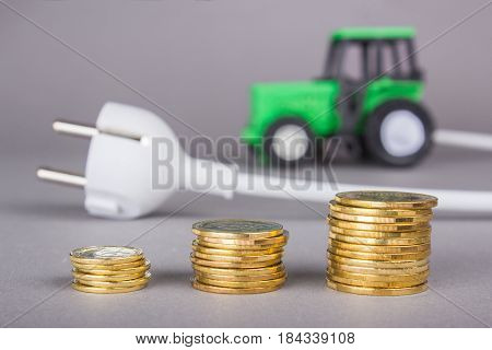 The electric tractor is charged from the outlet. Ecotech on the farm. A white plug from the socket is connected to a tractor on a gray background. A stack of coins savings