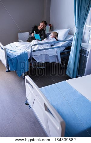 Happy girl on a bed reading book with her father in hospital