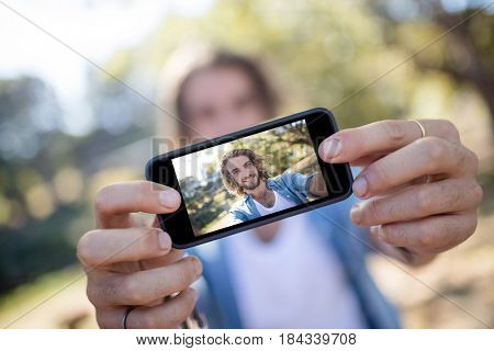 Man taking picture of himself on mobile phone in park