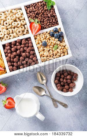 Milk jug and variety of cold quick breakfast cereals with berries in white wooden box, healthy eating concept, top view.