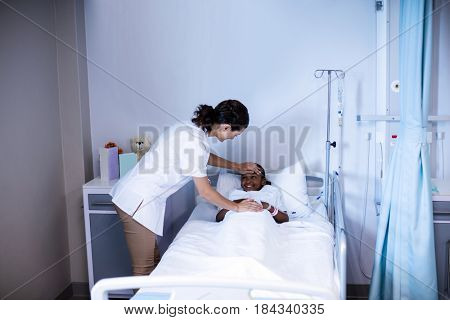 Female doctor checking patient fever in ward at hospital