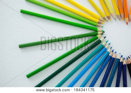 Close-up of colored pencils arranged in semi circle on white background