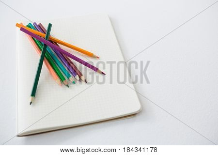 Colored pencils kept on the book on white background