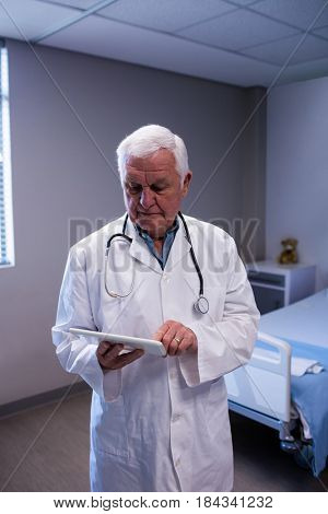 Male doctor using digital tablet in ward at hospital
