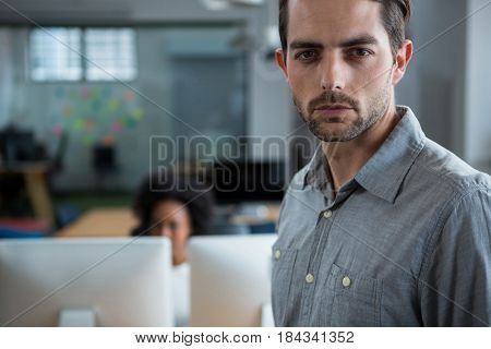 Portrait of a serious man standing in creative office