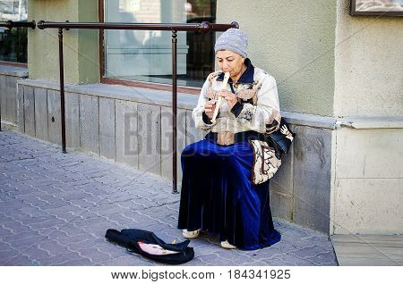 April 29 2017. Russia. Rostov-on-Don. An adult gypsy woman musician plays a flute on a pipe in a city street collecting donations from passers-by.