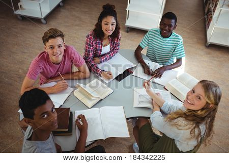 High angle view of happy classmates studying in library at school