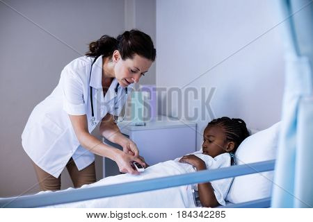 Female doctor checking patient sugar level in hospital