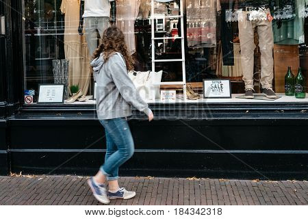 Delft Netherlands - August 3 2016: Woman going window shopping at fashion store in the historical city centre of Delft