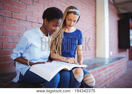 Attentive schoolgirls reading book in school campus
