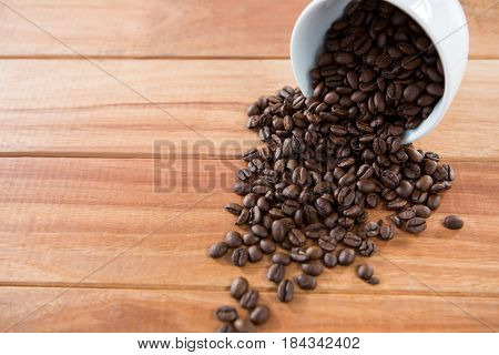 Roasted coffee beans spilling out of cup on wooden table