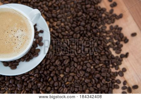 Cup of coffee with roasted coffee beans on wooden background
