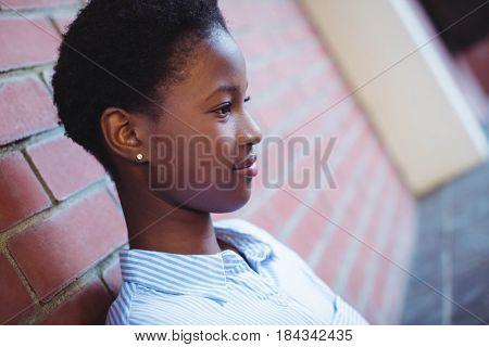 Thoughtful schoolgirl sitting against brick wall in school campus