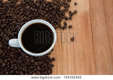 Cup of black coffee with roasted coffee beans on wooden background