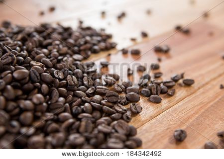 Roasted coffee beans spilled on wooden table