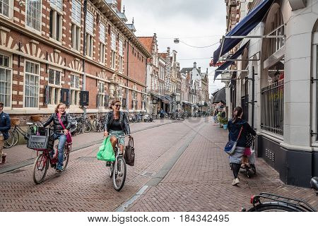 Haarlem Netherlands - August 3 2016: Picturesque commercial street of Haarlem near the cathedral with cyclists and people