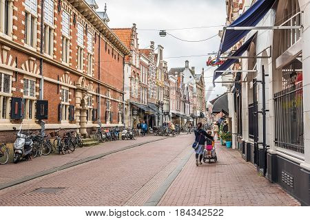 Haarlem Netherlands - August 3 2016: Picturesque commercial street of Haarlem near the cathedral with bicycles and people