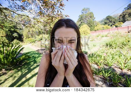 Woman blowing nose with tissue paper in park