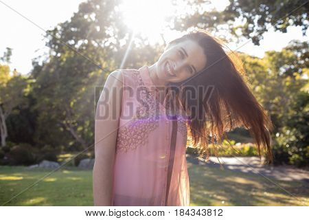 Portrait of beautiful woman swaying her hair in the park on a sunny day