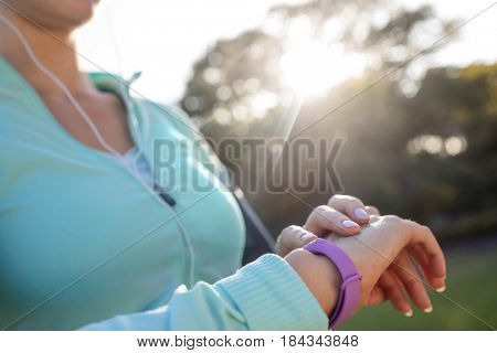 Mid section of female jogger checking her fitness band in the park