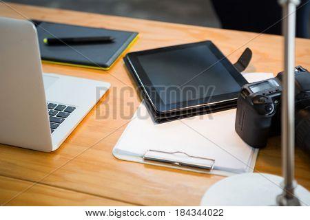 Close-up of laptop, digital tablet and digital camera on desk