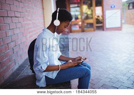 Schoolgirl listening music on mobile phone in school campus