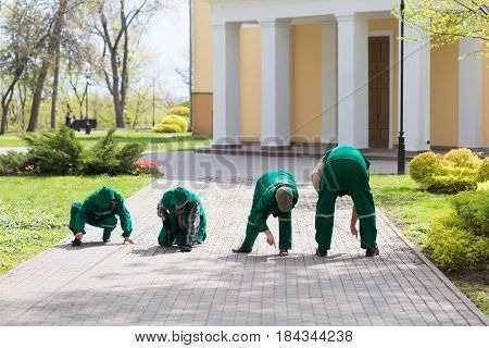 GOMEL BELARUS - 29 April 2017: Workers of the city park cleaning the paving slab